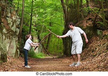 Father and son playing with sticks on a hike in a beautiful...