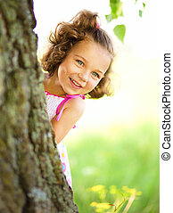 Cute little girl is playing hide and seek
