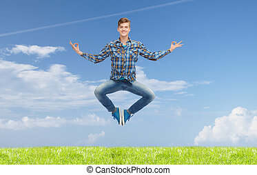smiling young man jumping in air - happiness, freedom,...