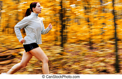 Fall Forest Runner - Beautiful young woman running in a fall...