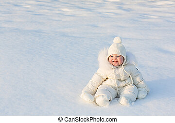Beautiful baby in a white snow suit sitting on fresh snow on...