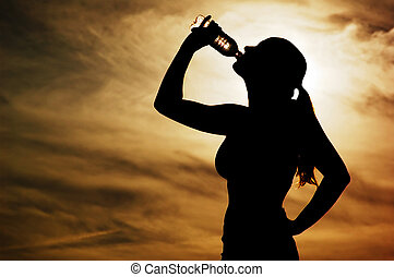 Sunset Thirst - Beautiful young sporty woman drinking in...