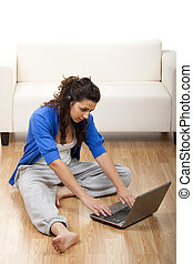 Girl using a laptop - Portrait of a girl seated on floor and...