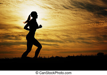 Sunset Runner - Beautiful young woman running in front of a...