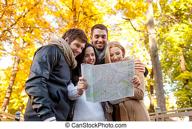 group of friends with map outdoors - travel, vacation,...