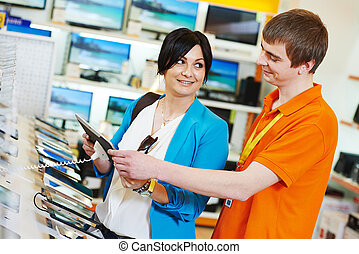 woman shopping at electronics supermarket - Young woman...
