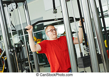man doing back exercises at fitness gym