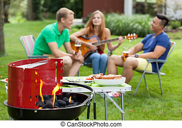 Girl playing the guitar on a barbecue