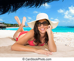 girl relaxing lying on a towel - in a tropical resort