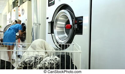 Woman gets clean clothes from washing machine in laundry