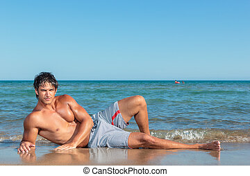 Portrait of a handsome young muscular man in swimwear