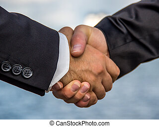Business handshake infront of ocean - A photograph of...