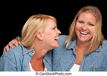 Two Beautiful Sisters Laughing Isolated on a Black...