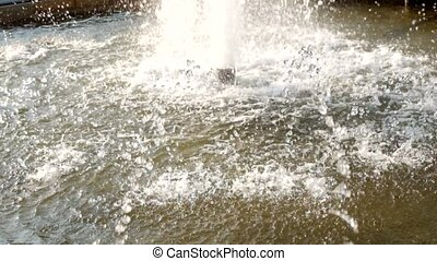 Wter falling down in fountain, ripples on water surface.