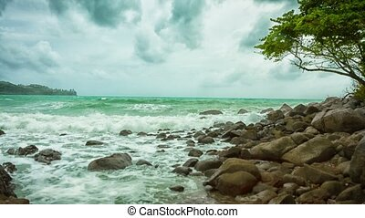 Rocky deserted shore of the tropical sea on a cloudy day