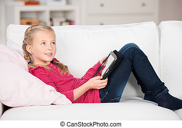 kid with digital pad lying on sofa - modern kid with digital...