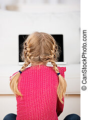 little girl with pigtails looking at laptop - blond little...