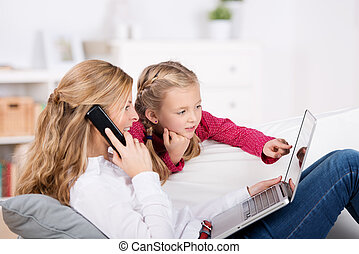 Mother And Daughter With Laptop And Phone - Mother and...