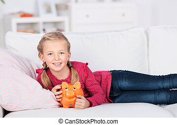 girl lying on sofa holding piggy bank in her hand