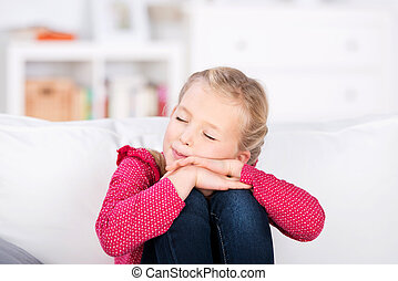 little girl dreaming with closed eyes at home