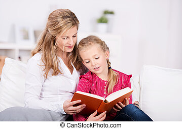 Mother And Daughter Reading Book - Mother and young daughter...