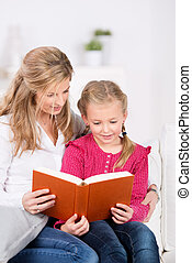 Mother And Daughter Reading Book together - Mother and young...