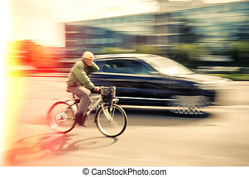 Cyclist and a car on the street. People hurrying about their...