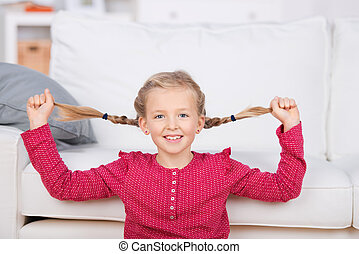 Playful Girl Pulling Her Pigtails At Home - Portrait of a...