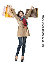 Winter shopping woman of Asian holding bags, full length...