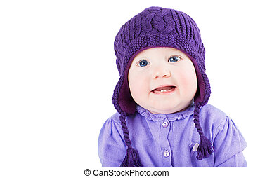 Beautiful baby girl with blue eyes wearing a purple sweater and knitted hat, isolated on white