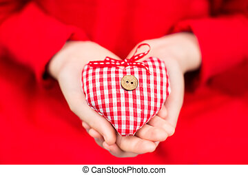 Hands of a child holding a plaid red-white textile heart with a wooden button