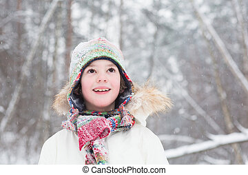 Portrait of a cute boy in a colorful knitted hat and scarf...