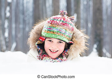 Portrait of a happy laughing child playing in the snow