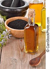 Nigella sativa oil. - Nigella sativa oil in a bottle and...
