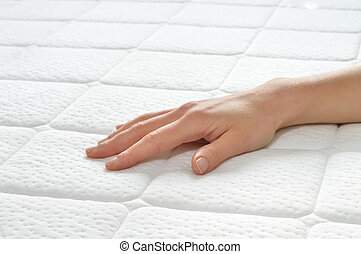 Choosing mattress and bed. Close-up of female hand touching...