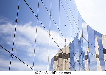 glass panes on facade of trade building reflecting blue sky...