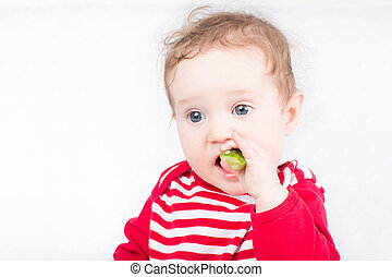 Funny baby eating a cucumber