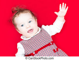 Little baby girl in a festive dress singing and dancing