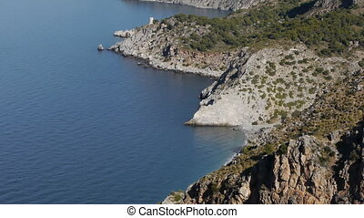blue sea surrounded by cliffs between the provinces of...