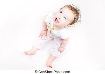Beautiful little girl with curly hair sitting on white...