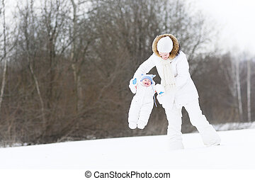 Young mother playing with her baby on a snowy winter day