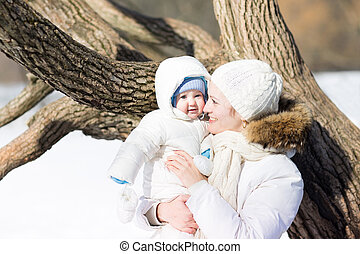 Young mother with a little baby walking in a snowy park