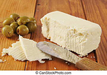 Feta cheese and olives - a block of feta cheese with green...