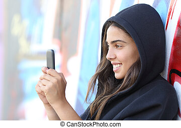Skater style teen girl reading happy her smart phone with an...