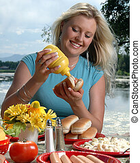 Summer Picnic - A woman squeezing mustard on a hot dog at a...