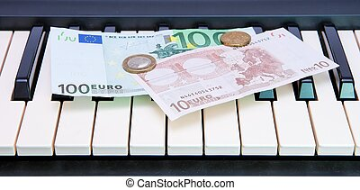 Euro bills and coins on electric organ keyboard