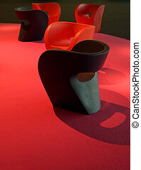 Many plastic design couches on magenta red carpet - Several...