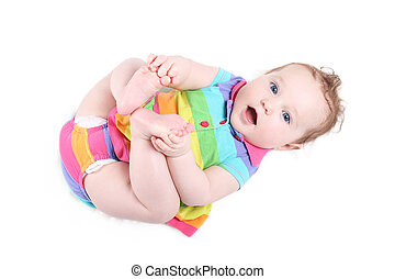 Funny baby girl playing with her feet, isolated on white