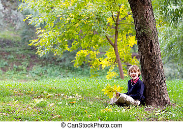 Little school boy sitting under a colorful autumn tree