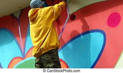 View of young graffiti artist at work